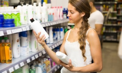 woman choosing sulfate free shampoo featured