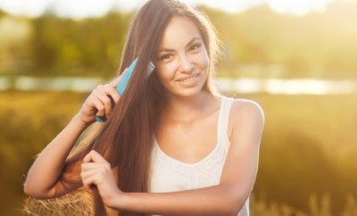 young girl combing hair featured